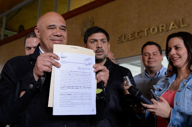 Venezuelan opposition spokesman Jesus Torrealba shows a document after delivering the application for the recall referendum at the CNE headquarters in Caracas, on August 2, 2016 (AFP Photo/Federico Parra)