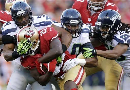 San Francisco 49ers running back Frank Gore (21) is tackled by Seattle Seahawks middle linebacker Bobby Wagner (54), outside linebacker K.J. Wright (50) and free safety Earl Thomas (29) during the first quarter of an NFL football game in San Francisco, Thursday, Oct. 18, 2012. (AP Photo/Marcio Jose Sanchez)