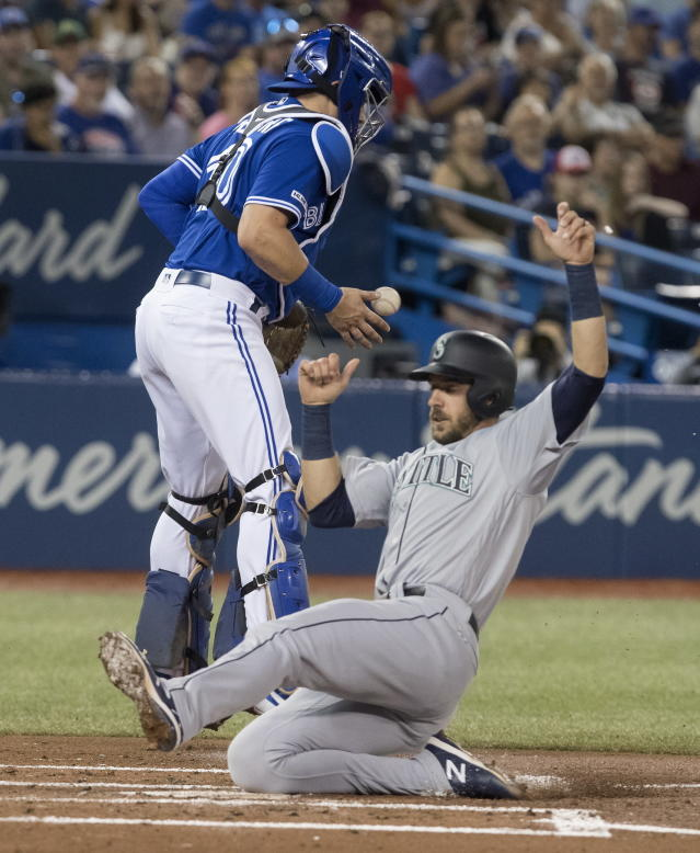 Seattle Mariners' Austin Nola slides safe into home plate as Toronto Blue Jays catcher Reese McGuire bobbles the ball during second inning American League MLB baseball action in Toronto, Saturday, Aug. 17, 2019. (Fred Thornhill/The Canadian Press via AP)