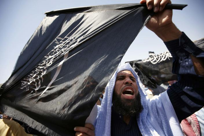"""FILE - In this Saturday, April 21, 2012 file photo, a follower of Egyptian Muslim cleric and former candidate for the presidency Hazem Abu Ismail holds an Islamist flag that reads, """"no god but Allah, Muhammad is the Prophet,"""" during a demonstration in Tahrir Square, Cairo, Egypt. Internal divisions are threatening to unravel Egypt's second biggest political party, the political arm of the ultraconservative Salafis, the country's most hardline Islamist movement. Now its leaders are split over whether Muslim clerics or more pragmatic politicians should be steering the movement. (AP Photo/Fredrik Persson, File)"""