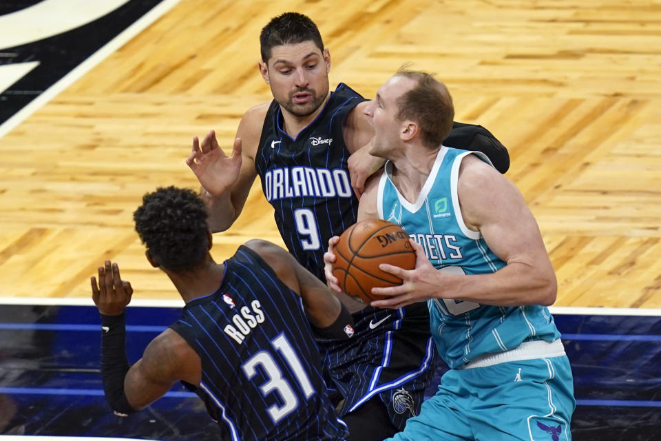 Charlotte Hornets center Cody Zeller, right, drives to the basket against Orlando Magic guard Terrence Ross (31) and center Nikola Vucevic (9) during the second half of an NBA basketball game, Monday, Jan. 25, 2021, in Orlando, Fla. (AP Photo/John Raoux)
