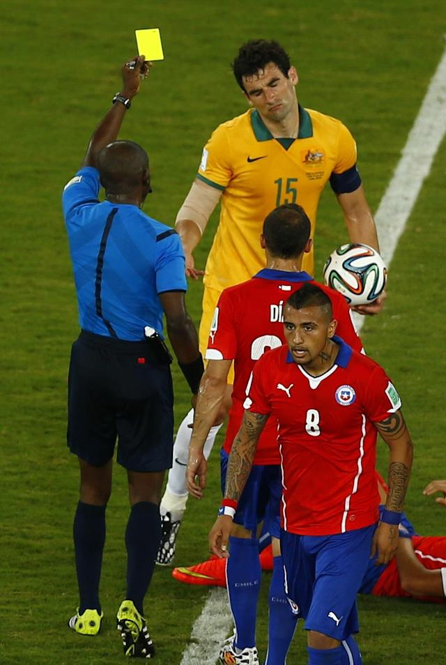 Referee Noumandiez Doue of Ivory Coast (in blue) shows the yellow card to Australia's Mile Jedinak (15) during the team's 2014 World Cup Group B soccer match against Chile at the Pantanal arena in Cuiaba June 13, 2014. REUTERS/Amr Abdallah Dalsh (BRAZIL - Tags: SOCCER SPORT WORLD CUP)