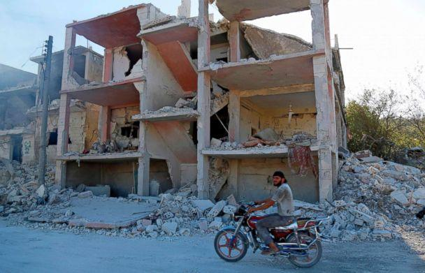 PHOTO: A Syrian man rides a motorcycle past a destroyed building in an area that was hit by a reported air strike in the district of Jisr al-Shughur, in the Idlib province, on Sept. 4, 2018. (AFP/Getty Images)
