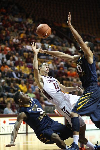 West Virginia forward Remi Dibo, right, knocks the ball away from Virginia Tech guard Devin Wilson (11), center, as West Virginia's Juwan Staten, bottom, looks up at the action during the first half of an NCAA college basketball game in Blacksburg, Va., Tuesday, Nov. 12, 2013. (AP Photo/The Roanoke Times, Daniel Lin)