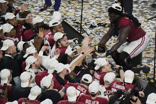 Alabama offensive lineman Alex Leatherwood holds the trophy for his teammates to touch after an NCAA College Football Playoff national championship game against Ohio State, Tuesday, Jan. 12, 2021, in Miami Gardens, Fla. Alabama won 52-24. (AP Photo/Wilfredo Lee)