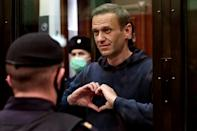 Navalny gestures a heart shape from inside a glass cell during a court hearing in Moscow
