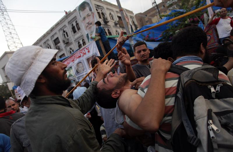 Supporters of Egypt's ousted President Mohammed Morsi carry an injured man to a field hospital following clashes with security forces at Nasr City, where pro-Morsi protesters have held a weeks-long sit-in, in Cairo, Egypt, Saturday, July 27, 2013. Police fired tear gas to disperse hundreds of Morsi supporters, setting off clashes that lasted for hours and left tens of people dead. (AP Photo/Khalil Hamra)