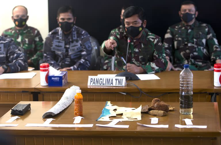 Indonesian Military chief Hadi Tjahjanto, center, talks to media as they display debris found in the waters during a search operation for the Indonesian Navy submarine KRI Nanggala at Ngurah Rai Military Air Base in Bali, Indonesia on Saturday, April 24, 2021. Indonesia's navy on Saturday said items were found from a missing submarine, indicating the vessel with 53 crew members had sank and there was no hope of finding survivors.(AP Photo/Firdia Lisnawati)