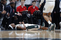 Michigan State's Cassius Winston, bottom, reacts in front of the Ohio State bench after being fouled on a three-point basket during the first half of an NCAA college basketball game, Sunday, March 8, 2020, in East Lansing, Mich. (AP Photo/Al Goldis)