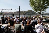 Guests enjoy the sunny weather as they sit in front of a restaurant after the Hungarian government allowed to reopen outdoor terraces in Budapest