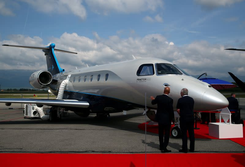FILE PHOTO: Visitors talk in front of the Praetor 600 aircraft on the Embraer stand in 2019 during the EBACE at Cointrin Airport in Geneva