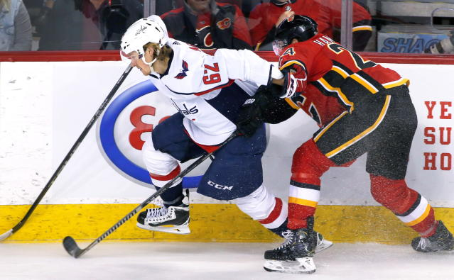 Washington Capitals left wing Carl Hagelin (62) moves along the boards as Calgary Flames defenseman Travis Hamonic (24) defends during the second period of an NHL hockey game Tuesday, Oct. 22, 2019, in Calgary, Alberta. (Larry MacDougal/The Canadian Press via AP)