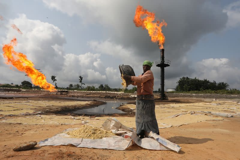 A woman empties a plastic bowl filled with tapioca close to a gas flaring furnace in Ughelli, Delta State