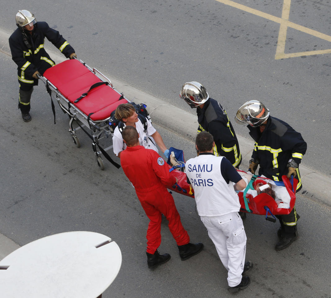 Rescue workers transport a victim from a train that derailed in Bretigny sur Orge, south of Paris, Friday July, 12, 2013. A packed passenger train skidded off its rails after leaving Paris on Friday, leaving seven people believed dead and dozens injured as train cars slammed into each other and overturned, authorities said. (AP Photo/Jacques Brinon)