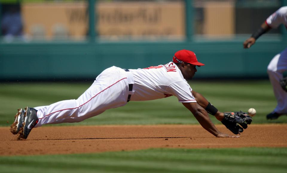 Los Angeles Angels third baseman Chris Nelson cannot reach a ball hit for a fielders' choice by Houston Astros' Carlos Corporan during the first inning of their baseball game on Sunday, Aug. 18, 2013, in Anaheim, Calif. Astros' Chris Carter was thrown out at second on the play. (AP Photo/Mark J. Terrill)
