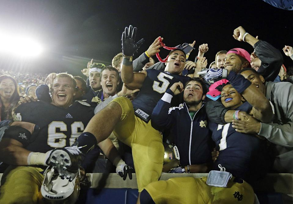 Notre Dame's Chris Watt (66), Manti Te'o (5) and TJ Jones (7) celebrate with fans after Notre Dame defeated Michigan, 13-6, in an NCAA college football game in South Bend, Ind. on Sept. 22, 2012. (AP Photo/Darron Cummings)