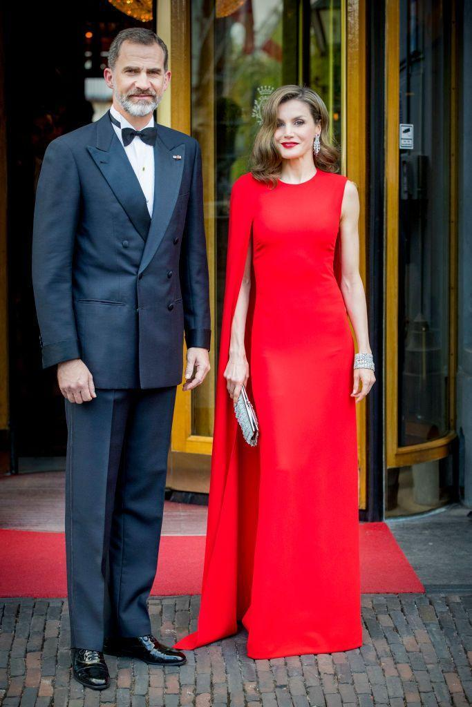 """<p><a href=""""https://www.townandcountrymag.com/society/tradition/g10297690/queen-letizia-style/"""" rel=""""nofollow noopener"""" target=""""_blank"""" data-ylk=""""slk:Queen Letizia"""" class=""""link rapid-noclick-resp"""">Queen Letizia</a> looked chic in a red Stella McCartney gown with one-shouldered cape detail. Letizia and King Felipe dressed up for King Willem-Alexander of the Netherlands' 2017 birthday party in The Hague. <br></p>"""
