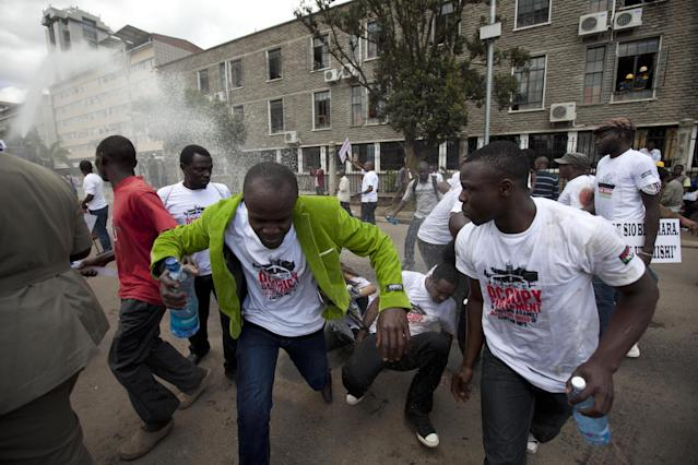 "Kenyan demonstrators run after police release tear gas, in Nairobi, Kenya, Tuesday, May 14, 2013. Police fired tear-gas, water cannons and swung their batons at protesters gathered outside Kenya's parliament building to pile pressure on the country's legislators to drop demands for a salary increment. About 250 people carrying placards and banners marched through the Nairobi's city center and staged a sit in at the entrance legislators use to enter parliament. There the protesters released about two dozen piglets and a pig to symbolize ""the greed of the country's legislators."" (AP Photo/Sayyid Azim)"