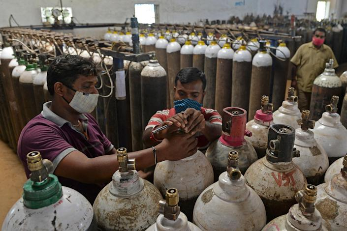 "At a facility on the outskirts of Chennai on April 24, workers check medical oxygen cylinders that will be transported to hospitals.<span class=""copyright"">Arun Sankar—AFP/Getty Images</span>"