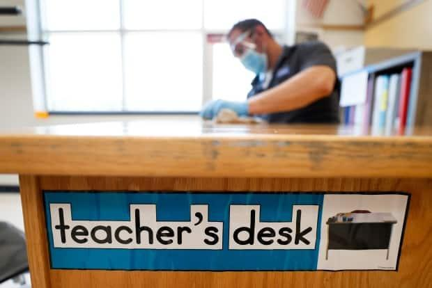 A custodian cleans a teacher's desk in Des Moines, Iowa. The chair of Ottawa's largest school board wants the province to prioritize vaccinating education workers.