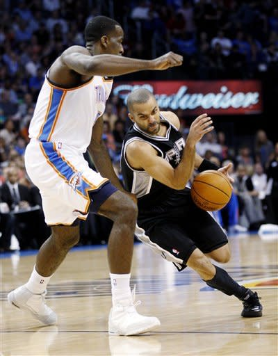 San Antonio Spurs guard Tony Parker, right, of France, drives around Oklahoma City Thunder center Kendrick Perkins, left, in the first quarter of an NBA basketball game in Oklahoma City, Friday, March 16, 2012. (AP Photo/Sue Ogrocki)