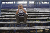 A soccer fan mourns the death of Diego Maradona at the stadium of the soccer club Gimnasia y Esgrima, coached by Maradona, in La Plata, Argentina, Wednesday, Nov. 25, 2020. The Argentine soccer great who was among the best players ever and who led his country to the 1986 World Cup title before later struggling with cocaine use and obesity, died from a heart attack on Wednesday at his home in Buenos Aires. He was 60. (AP Photo/Maria Paula Avila)