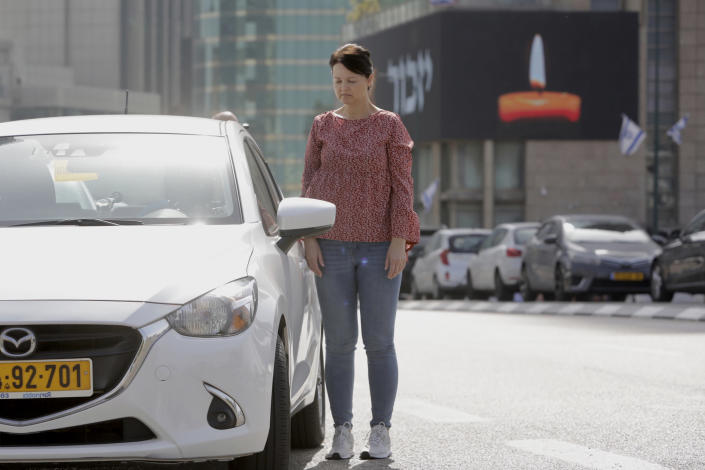 Israelis stand next to their cars as sirens mark a nationwide moment of silence in remembrance of the 6 million Jewish victims of the Holocaust, in Tel Aviv, Israel, Thursday, April 8, 2021. (AP Photo/Sebastian Scheiner)
