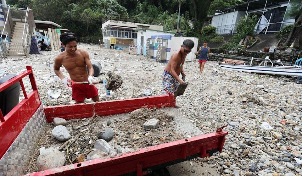 Two workers begin removing debris from Silverstrand Beach. Photo: May Tse