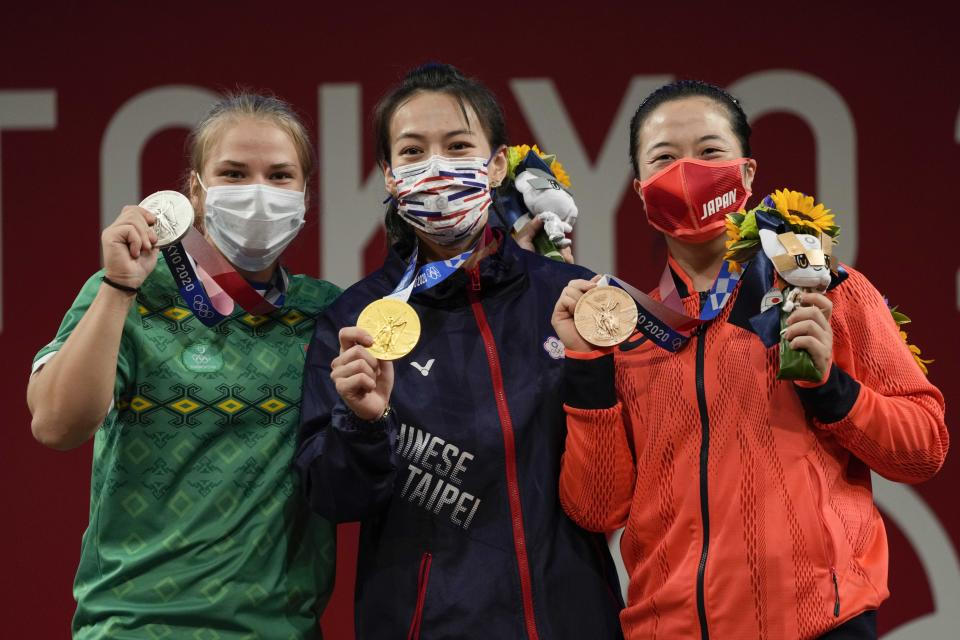 Gold medalist Kuo Hsing-Chun of Taiwan, center, is flanked by silver medalist Polina Guryeva of Turkmekistan, left and bronze medalist Mikiko Andoh of Japan on the podium after the women's 59kg weightlifting event, at the 2020 Summer Olympics, Tuesday, July 27, 2021, in Tokyo, Japan. (AP Photo/Luca Bruno)