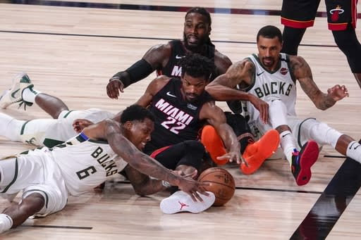 Milwaukee Bucks' Eric Bledsoe and Miami Heat's Jimmy Butler go after a loose ball during the second half of an NBA conference semifinal playoff basketball game Sunday, Sept. 6, 2020, in Lake Buena Vista, Fla. (AP Photo/Mark J. Terrill)