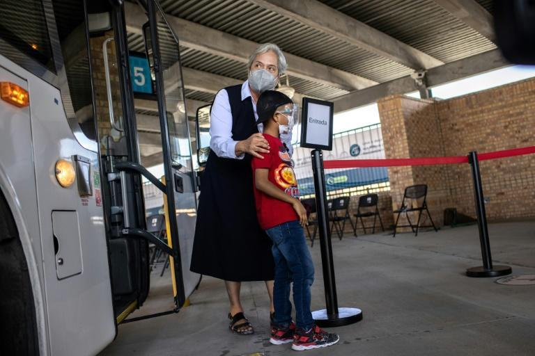 Sister Norma Pimentel of Catholic Charities escorts a child who has requested asylum upon arriving in the United States on February 26, 2021 in Brownsville, Texas