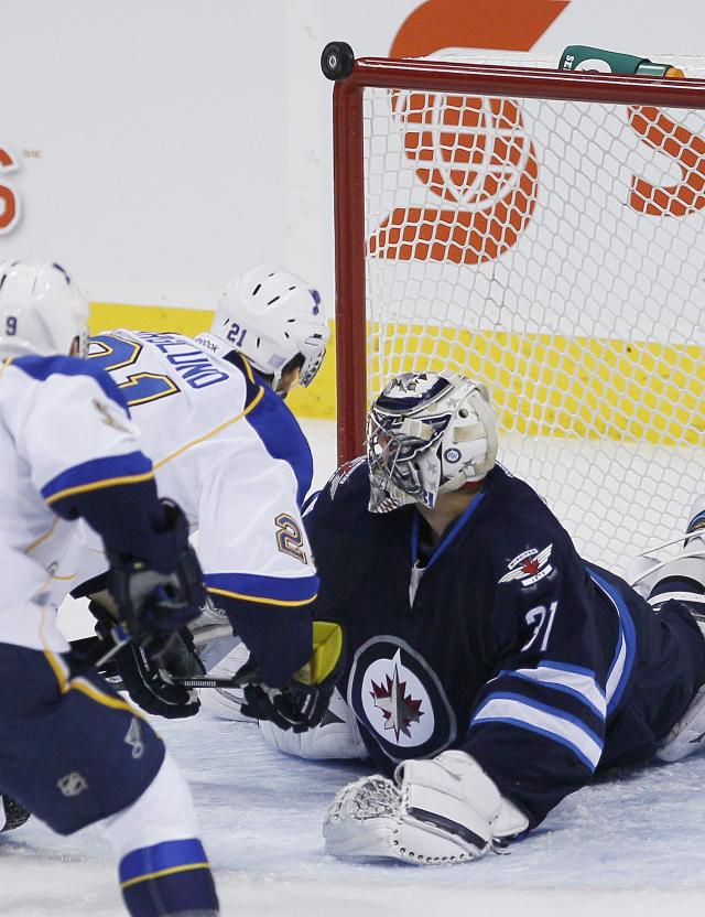 St. Louis Blues' Patrik Berglund (21) and Winnipeg Jets goaltender Ondrej Pavelec (31) watch as the rebound goes off the post during the first period of an NHL hockey game, Friday, Oct. 18, 2013 in Winnipeg, Manitoba. (AP Photo/The Canadian Press, John Woods)