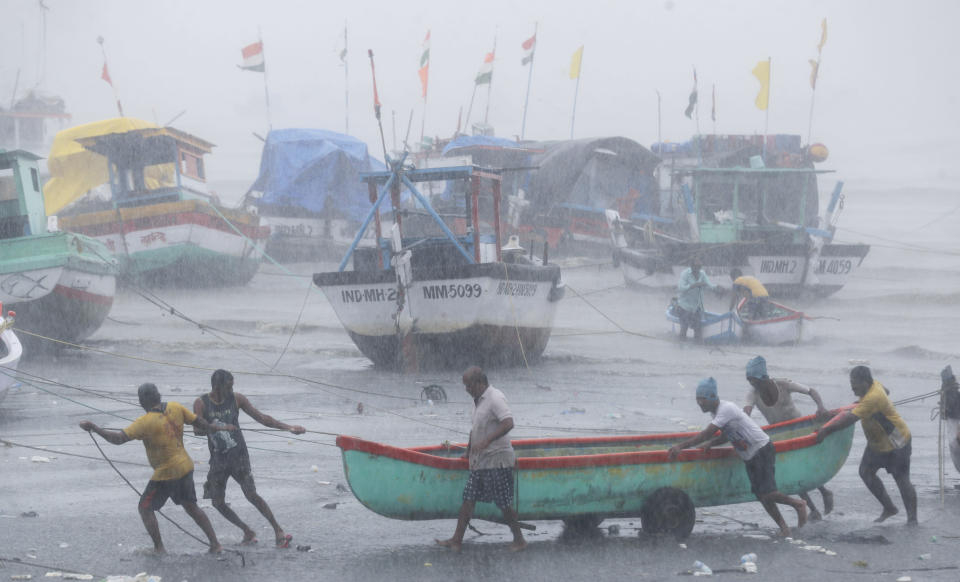 Fishermen try to move a fishing boat to a safer ground on the Arabian Sea coast in Mumbai, India, Monday, May 17, 2021. Cyclone Tauktae, roaring in the Arabian Sea was moving toward India's western coast on Monday as authorities tried to evacuate hundreds of thousands of people and suspended COVID-19 vaccinations in one state. (AP Photo/Rafiq Maqbool)