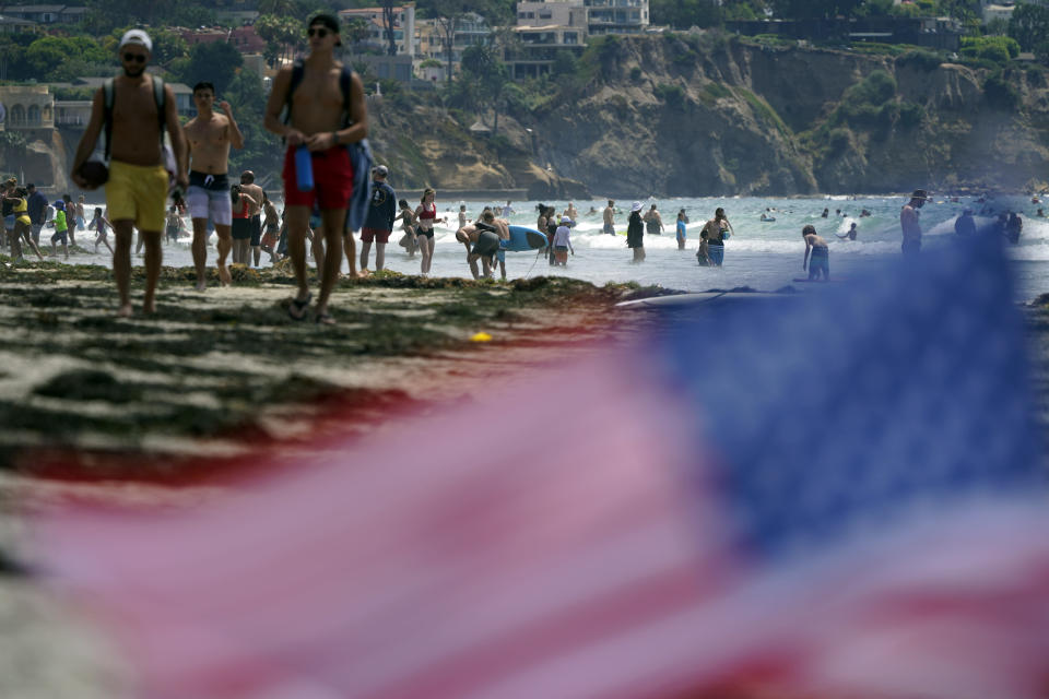 FILE - In this July 1, 2021, file photo, people walk along La Jolla Shores beach as Independence Day weekend nears in San Diego. Americans enjoying newfound liberty are expected to travel and gather for cookouts, fireworks and family reunions over the Fourth of July weekend in numbers not seen since pre-pandemic days. (AP Photo/Gregory Bull, File)