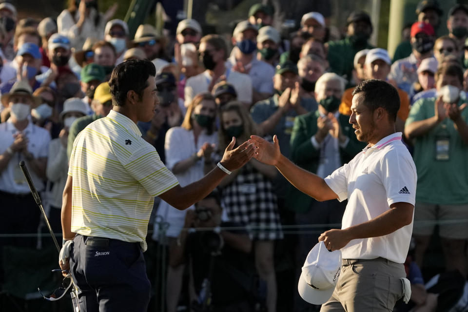Hideki Matsuyama, of Japan, shakes hands with Xander Schauffele on the 18th hole after winning the Masters golf tournament on Sunday, April 11, 2021, in Augusta, Ga. (AP Photo/Gregory Bull)