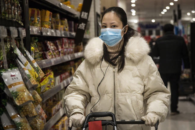 A resident of Wuhan, the epicentre of the coronavirus Covid-19 outbreak, wears a protective mask while shopping on 12 February. (Getty Images)