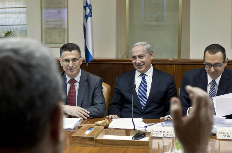Israeli Prime Minister Benjamin Netanyahu, second right, laughs as Defense Minister Ehud Barak, back to camera, makes a joke that Netanyahu should give fair time to the opposition in political statements, as Netanyahu chairs the weekly cabinet meeting in his Jerusalem offices, Sunday, Oct. 14, 2012. Israel's Cabinet announced January 22, 2013 as the date for parliamentary elections, with Prime Minister Benjamin Netanyahu leading in the polls. (AP Photo/Jim Hollander, Pool)