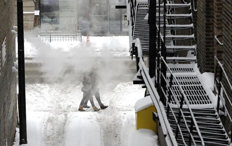 A couple walk through snowy streets in Chicago (AP)