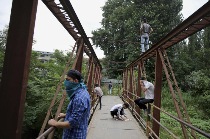 Kashmiri protesters monitor positions of Indian soldiers from a footbridge during a protest against the Indian government in Srinagar, India, Friday, Aug. 9, 2019. The predominantly Muslim area has been under an unprecedented security lockdown and near-total communications blackout to prevent unrest and protests after India's Hindu nationalist-led government said Monday it was revoking Kashmir's special constitutional status and downgrading its statehood. (AP Photo/Altaf Qadri)