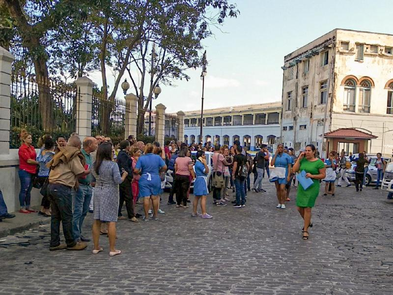 Workers leave their office building after the quake was felt in Havana, Cuba: AFP