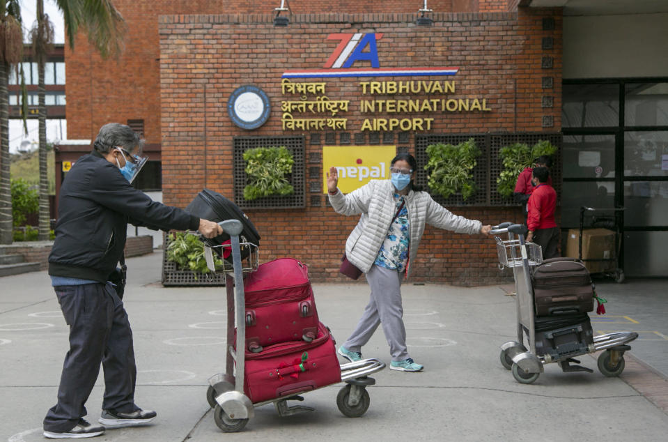 Passengers wearing face masks arrive to board departing flights at the Tribuvan International airport in Kathmandu, Nepal, Thursday, May 6, 2021. Thousands of passengers rushed to leave Nepal as the Himalayan nation halts all international flights from Thursday because of spiking cases of COVID-19. (AP Photo/Niranjan Shrestha)
