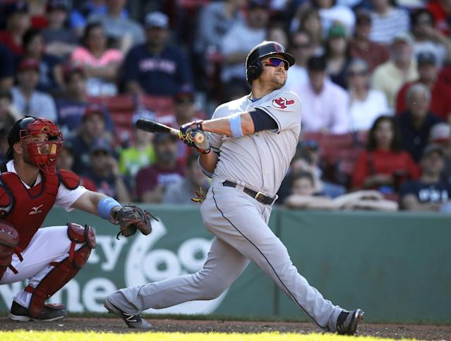 Cleveland Indians' Nick Swisher, right, hits a home run as Boston Red Sox catcher David Ross, left, looks on in the 11th inning of a baseball game, Sunday, June 15, 2014, in Boston. The Indians won 3-2 in 11 innings. (AP Photo/Steven Senne)