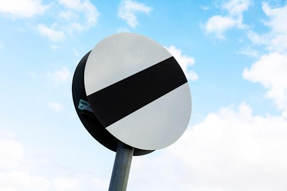 national speed limit applies road sign UK England against blue sky copy space clouds