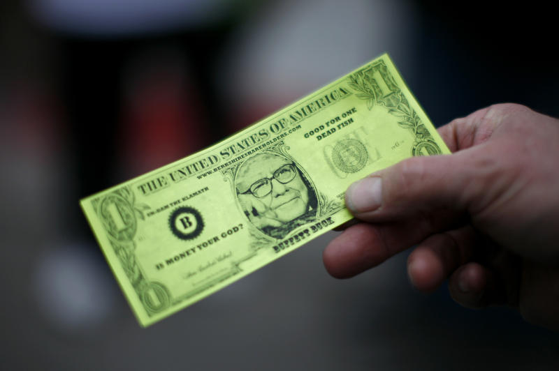 A Berkshire Hathaway shareholder hold a fake dollar bill with the face of billionaire financier and Berkshire Hathaway CEO Warren Buffett during the kick-off celebration at the annual Berkshire Hathaway shareholders meeting in Omaha, Nebraska May 2, 2008. REUTERS/Carlos Barria (UNITED STATES)