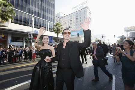 """Cast member Angelina Jolie and actor Brad Pitt wave at fans as they arrive at the premiere of """"Maleficent"""" at El Capitan theatre in Hollywood, California May 28, 2014. REUTERS/Mario Anzuoni"""