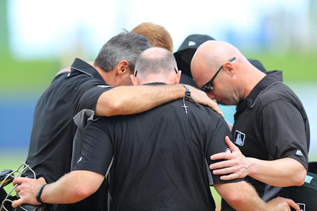 <p>Umpires pray at home plate before the baseball game between the Minnesota Twins and the Houston Astros at the Ballpark of the Palm Beaches in West Palm Beach, Fla., on Feb. 28, 2018. (Photo: Gordon Donovan/Yahoo News) </p>