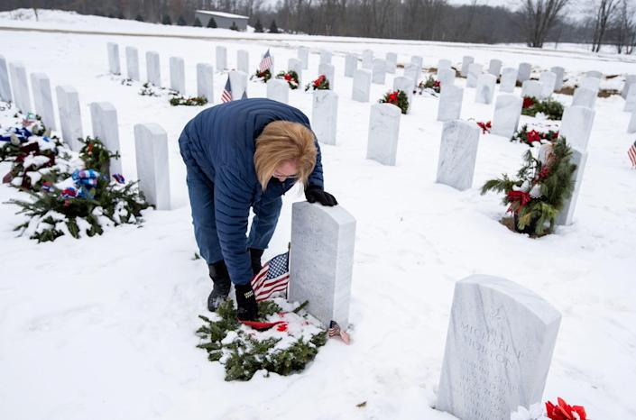 Judy Smith of Flint, Mich., wipes a frozen wreath Jan. 12 at the gravesite of her husband, Florian, who served as a medic in the Army during the Vietnam War, at Great Lakes National Cemetery in Holly. Smith says her husband, who had dementia, died prematurely because of the COVID-19 crisis, isolation and lack of visitors.