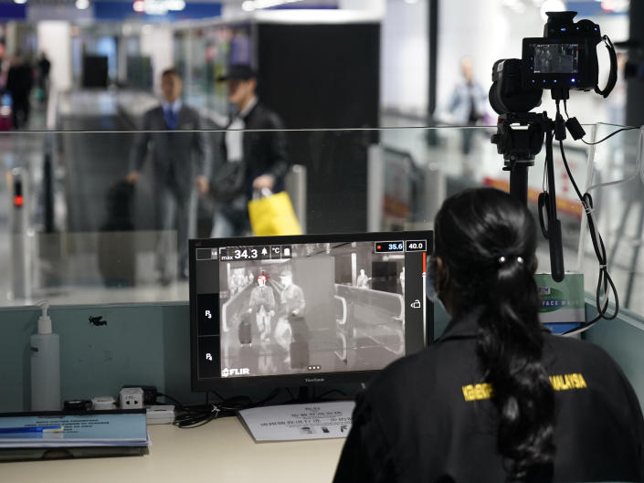 Health officials watch thermographic monitors at a quarantine inspection station at the Kuala Lumpur International Airport in Sepang, Malaysia, Tuesday, Jan. 21, 2020. Countries both in the Asia-Pacific and elsewhere have initiated body temperature checks at airports, railway stations and along highways in hopes of catching those at risk of carrying a new coronavirus that has sickened more than 200 people in China. (AP Photo/Vincent Thian)