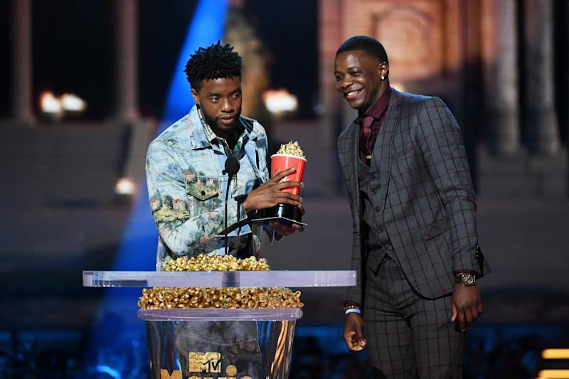 SANTA MONICA, CA - JUNE 16: Actor Chadwick Boseman (L), winner of the Best Hero award for 'Black Panther,' presents his trophy to James Shaw Jr. onstage during the 2018 MTV Movie And TV Awards at Barker Hangar on June 16, 2018 in Santa Monica, California. (Photo by Kevin Winter/Getty Images for MTV)