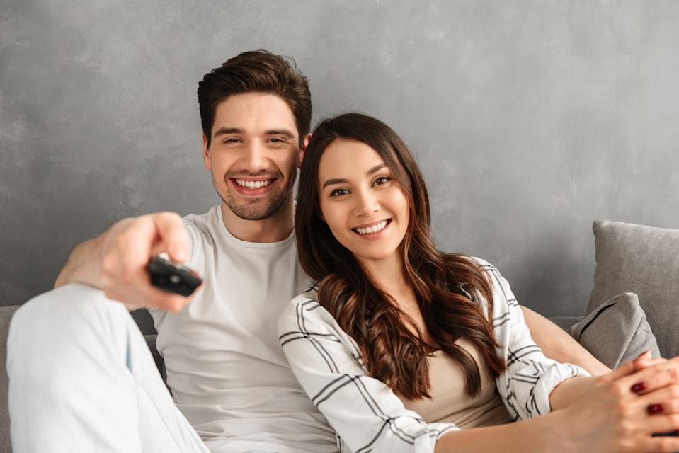Image closeup of young family sitting on sofa at home and looking at you showing remote control at camera